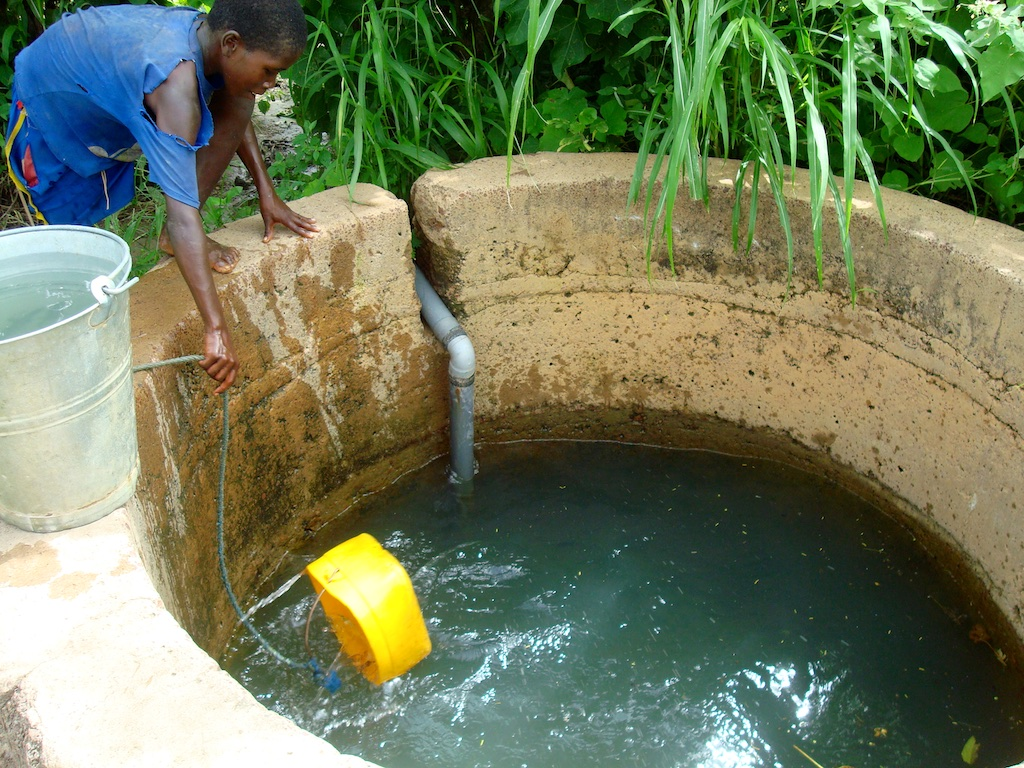 Rainwater catchment basins raise the water table, enabling villagers to tap local wells.