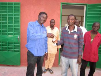Building architect handing keys to the Yelbouga CVD president.